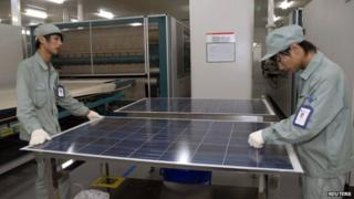 Employees work on a solar panel production line at Suntech Power Holdings headquarters in Wuxi, Jiangsu province