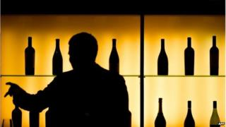 A man in silhouette picks a bottle of cognac