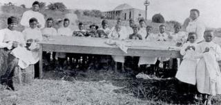 Nokutela Dube (standing on the right) gives a sewing class