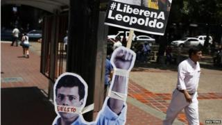 """People walk past cardboard figures of jailed opposition leader Leopoldo Lopez with his mouth covered with the word """"crime"""" during a gathering in support of him in Caracas on 4 June,, 2014"""
