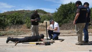 Police look remove a manhole cover on the edge of the 12-acre search site in Praia da Luz