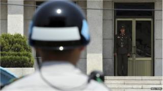 A North Korean soldier (R) looks south on the North side, as a South Korean soldier stands guard at the truce village of Panmunjom in the demilitarized zone which separates the two Koreas, May 14