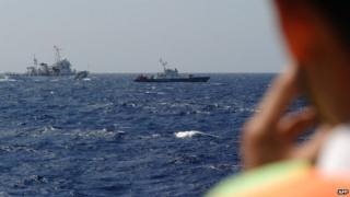 Picture taken from a Vietnam Coast Guard ship on May 14, 2014 shows a China Coast Guard ship (L) chasing a Vietnam Coast Guard vessel near to the site of a Chinese drilling oil rig being installed at the disputed water in the South China Sea