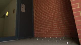 Studs on floor outside block of flats