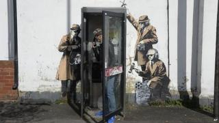 Man in phonebox with artwork on wall behind