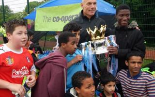 Howard Webb with children on football pitch