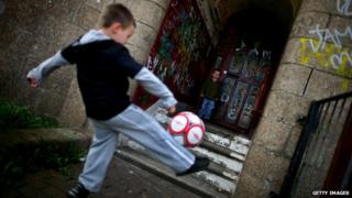Two boys playing football against a graffiti-strewn wall