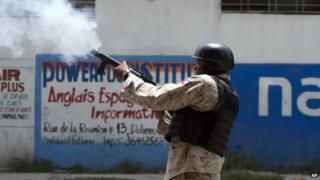 A National Police officer fires tear gas at protestors during an anti-government protest in Port-au-Prince, on 10 June, 2014