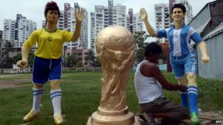 An Indian artist gives finishing touches to a clay idol of Argentine soccer player Lionel Messi (R) alongside a clay idol of Brazilian soccer player Neymar and a replica of FIFA World Cup for a football club, outside the workshop in Kolkata on June 10, 2014.