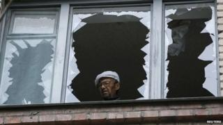 A man looks out of the broken window of his home in a residential building which was damaged by what locals say was overnight shelling by Ukrainian forces in the eastern town of Slaviansk
