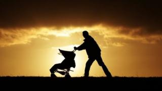 Father pushing buggy on Hampstead Heath in London