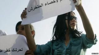 """A female protester holds a sign reading """"Yes to castrating the sexual harasser"""" in Cairo (11 June 2014)"""
