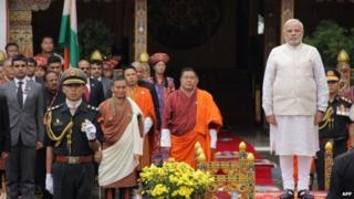 """PM Narendra Modi looks on with Bhutanese officials during a traditional """"chhipdrel"""" ceremony and to greet a guard of honour in Thimphu on June 15, 2014."""