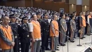 This screen grab taken from state broadcaster China Central Television (CCTV) footage shows eight prisoners (in orange and brown) standing at attention upon their arrival at the Intermediate People's Court in the Xinjiang capital Urumqi, 16 June 2014, for the trial of those accused in the attack in October 2013 in Beijing's Tiananmen Square that killed two tourists