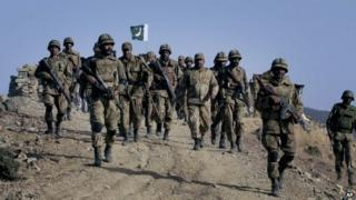 In this Tuesday, Nov. 17, 2009 file photo, Pakistani troops walk on a hilltop post near Ladha, a town in the Pakistani troubled tribal region of South Waziristan along the Afghan border.