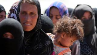 Displaced Iraqi women and children fleeing violence in Northern Iraq stand in line at a refugee centre near Arbil.