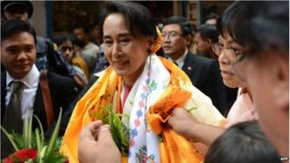 Myanmar opposition leader Aung San Suu Kyi is welcomed at a Buddhist monastery where she worked as an English teacher in 1973 in Kathmandu, on 16 June 2014.