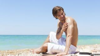Man applies sun cream on the beach