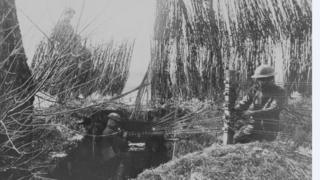 A field radio station, camouflaged with brush-wood and straw, in around 1918