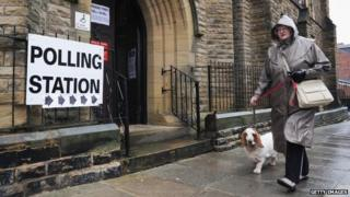 A woman walks her dog past a polling station in Teesside