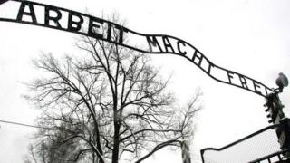 Visitors walk through the entrance gate of the Auschwitz Nazi concentration camp in Oswiecim, southern Poland 26 January 2005