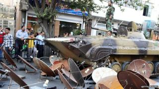 Iran security forces use an armoured vehicle to destroy satellite dishes