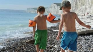 Two five-year old boys playing on a beach in East Sussex