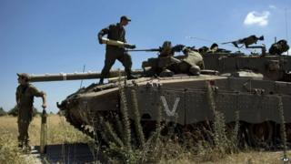 Israeli soldiers load shells in their tank in the Israeli-controlled Golan Heights, 22 June 2014