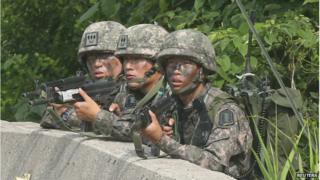 South Korean soldiers take position during a search and arrest operation at Goseong town as troops stand-off with a conscript soldier who shot and killed five comrades, on 23 June 2014.