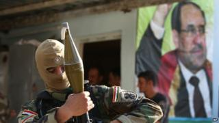 An Iraqi Shia gunman holds his RPG as he stands in front of a portrait of Iraqi Prime Minister Nouri Maliki in the Kirkuk province. Photo: 20 June 2014