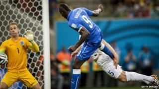 Italian striker Mario Balotelli heads the ball to score against England