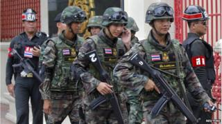 Soldiers patrol around the Royal Thai Army Headquarters as members of the Radio and Satellite Broadcasters gather in Bangkok on 18 June 2014.