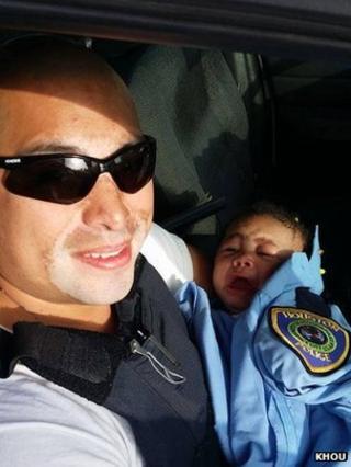 Officer Albert Pizana holds Genesis Haley