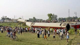 People gather around a passenger train that derailed in Bihar, near Chhapra town, India, Wednesday, June 25, 2014