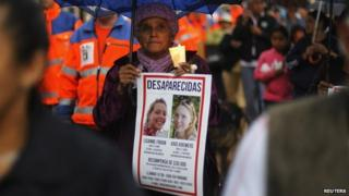 A local resident holds a candle and a missing person poster as she attends a public vigil to find two missing Dutch tourists in Boquete on 28 May, 2014