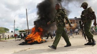 Kenyan police officers walk past a fire used to barricade a main road after unidentified gunmen recently attacked the coastal Kenyan town of Mpeketoni on 17 June 2014