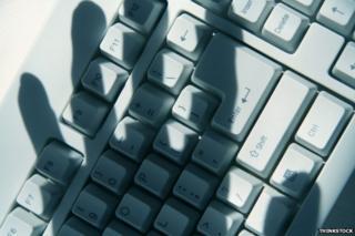 Shadow of hand over computer keyboard