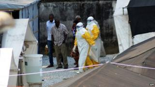 Health workers, wearing protective suits, walking in an isolation centre for people infected with Ebola at Donka Hospital in Conakry, Guinea, on 14 April 2014.