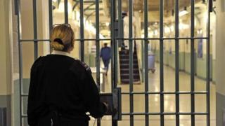 A prison officer locks a door at Wormwood Scrubs, a category B prison in London