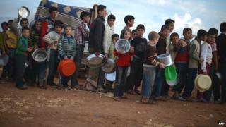 Internally displaced Syrian youths hold empty pots as they line up for food distribution