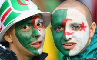 Two Algeria fans with their faces painted as the Algerian flag