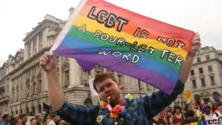 """Man holding banner which reads: """"LGBT is not a four-letter word"""""""
