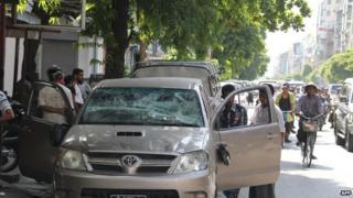 Local people hang around a damaged vehicle on a street of Mandalay in central Myanmar on 2 July 2014.