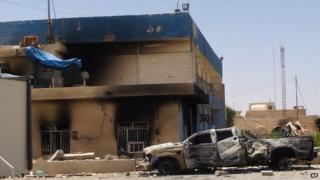 This photo taken on July 1, 2014, shows a burned police station from clashes between Isis fighters and Iraqi security forces in Tikrit