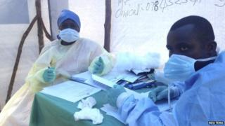 Government health workers are seen during the administration of blood tests for the Ebola virus in Kenema, Sierra Leone, on 25 June 2014