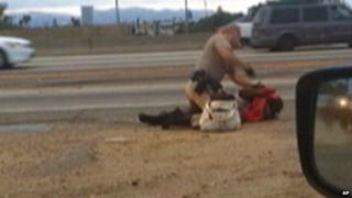 a California Highway Patrol officer straddles a woman while punching her in the head on the shoulder of a Los Angeles freeway 1 July 2014