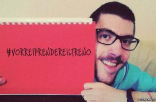 "Iacopo Melio holds up a sign saying ""#VorreiPrendereilTreno"", which means ""I would like to take the train"""