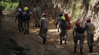 Firefighters walk towards a gold mine affected by a landslide to join rescue operations for eight miners who remain trapped in San Juan Arriba on 6 July, 2014