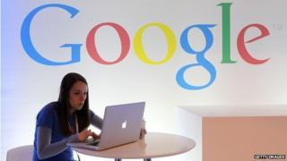Woman on laptop in front of google sign
