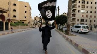 A member loyal to the Islamic State in Iraq and the Levant (Isis) waves an Isis flag in Raqqa, Iraq, 29 June 2014